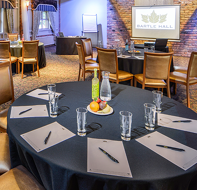 A photo showing a picture of delegates table at a business meeting at the Bartle Hall Hotel