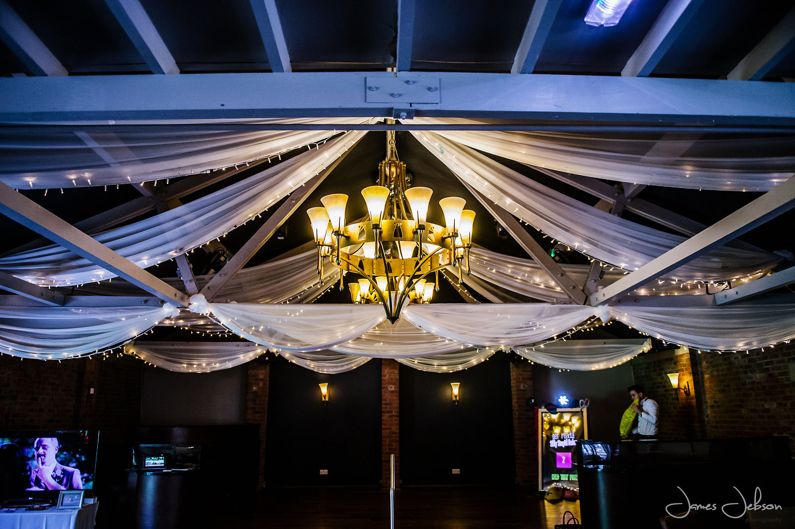 an image taken at night in one of their wedding suites showing a chandelier hanging from the ceiling